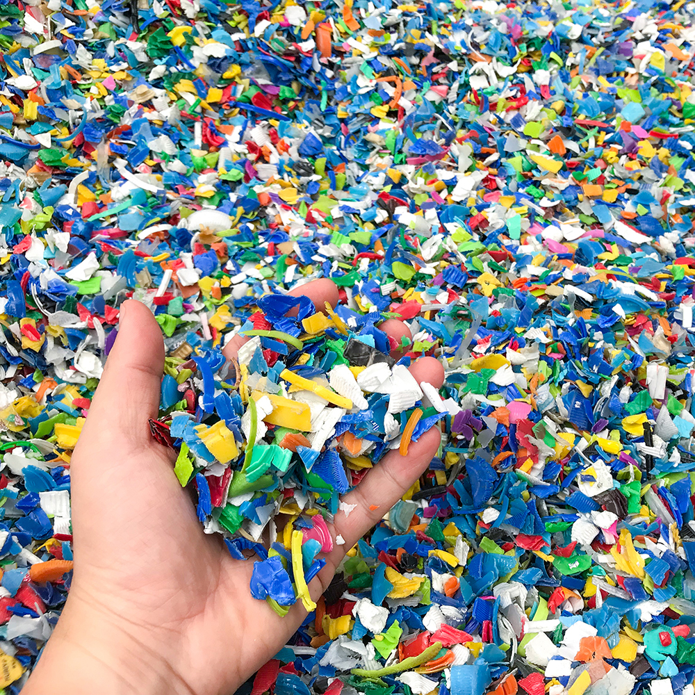 Hand holding Bottle flake,PET bottle flake,Plastic bottle crushed,Small pieces of cut colorful plastic bottles